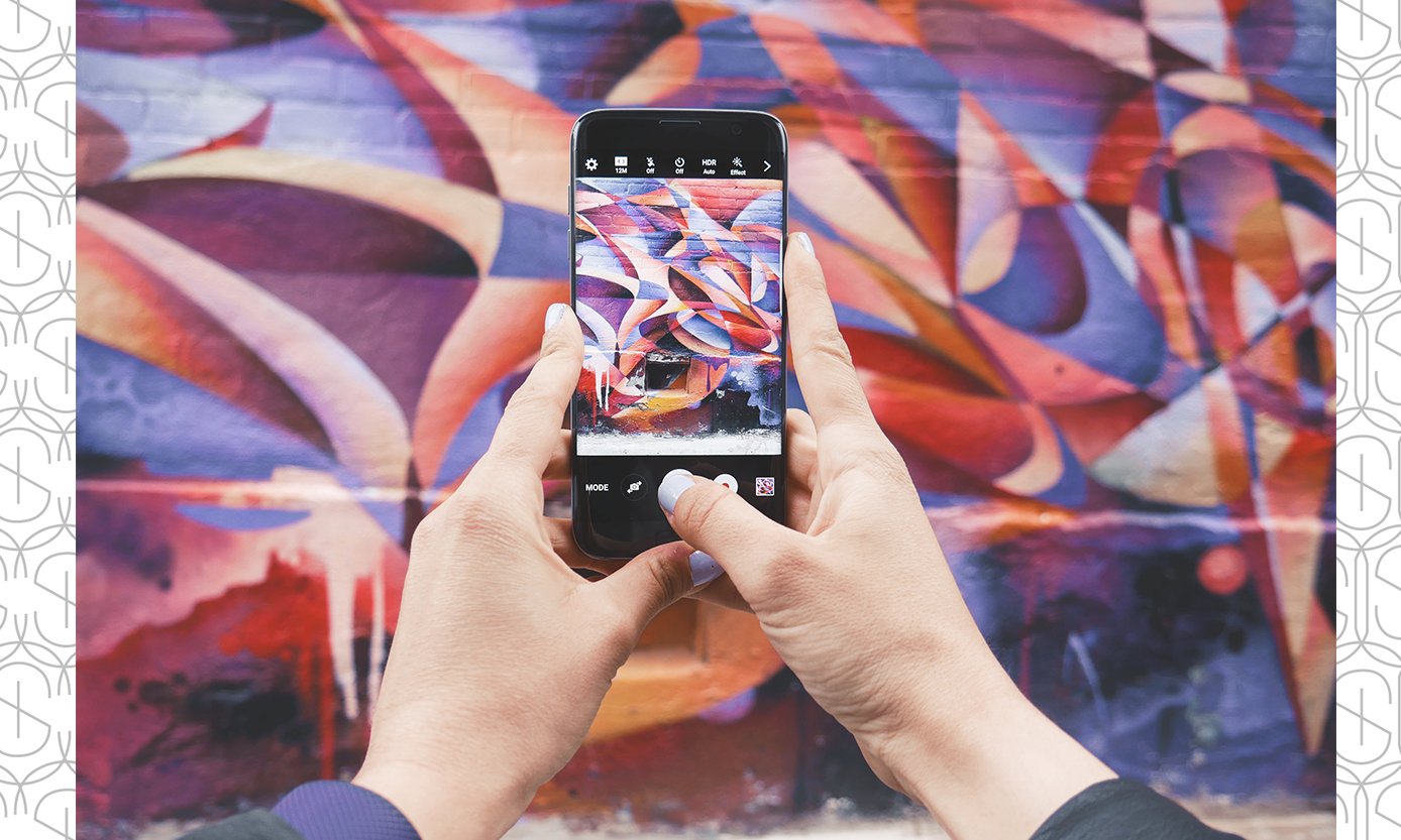 Hands holding an ipHone to take a picture of street art