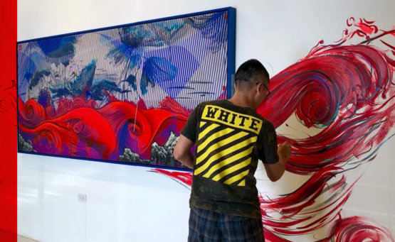 Na Wei working on a painting that covers the canvas and part of the wall.